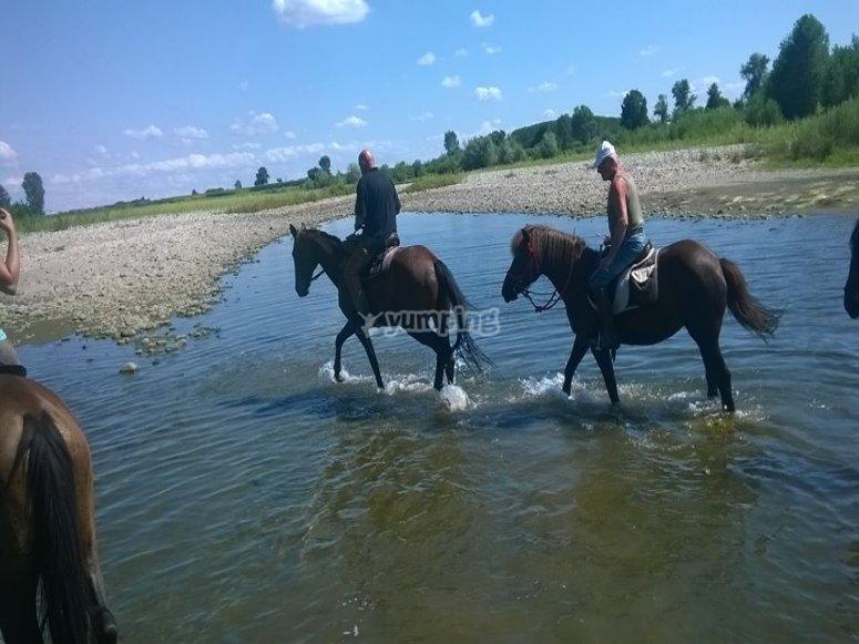 Guadando il fiume a cavallo