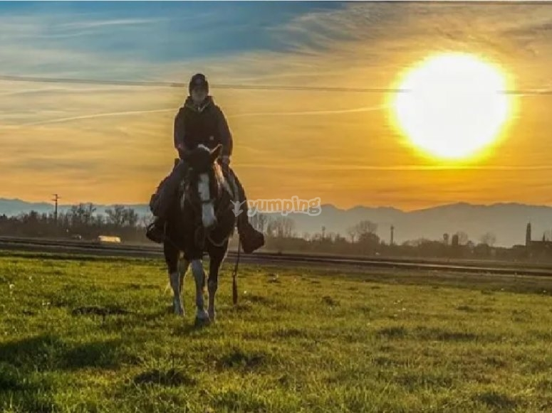 on horseback in the sunset of the po
