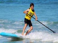 Un bambino tra le onde del mare. Il SUP è versatile!